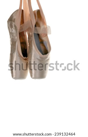 Ballet shoes hanging in front of a white background - stock photo