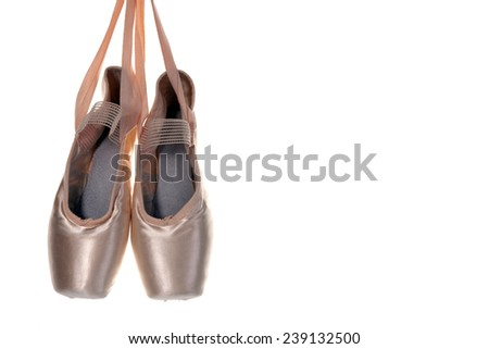 Ballet shoes hanging in front of a white background