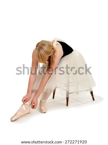 Ballet Student Ties Pointe Shoes to Prepare for Performance - stock photo