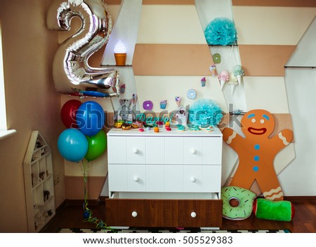 Ballon number two hangs over the sweet buffet put on the white wardrobe