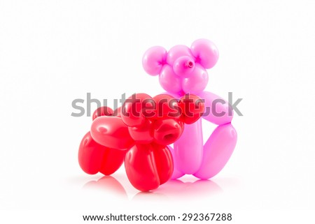 Balloon animal of red pig and pink bear action pose on white background.