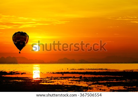Balloon flying into sunset over the sea. - stock photo