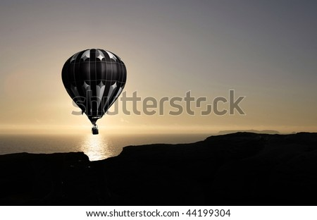 balloon flying into sunset over water