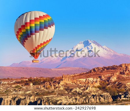 Balloon flying over rock landscape at Cappadocia Turkey with Erciyes Mountain. - stock photo