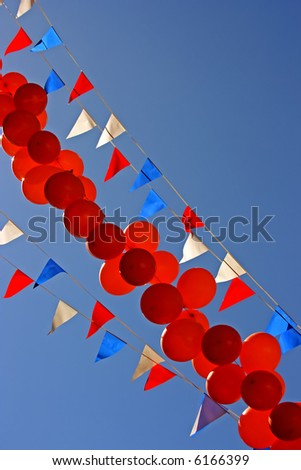 Balloons and flags against a blue sky