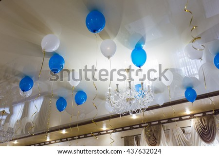Balloons floating above the ceiling of a large room - stock photo