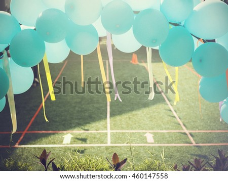 Balloons gate over the green grass field with lines for competition - stock photo