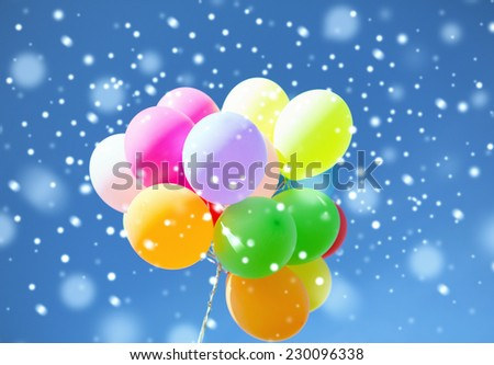 balloons, party, happiness and celebration concept - lots of colorful balloons in sky with snowflakes - stock photo