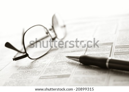 Ballpoint pen and reading glasses on newspaper jobs and help wanted employment classifieds ads section for an unemployment recovery job search - stock photo
