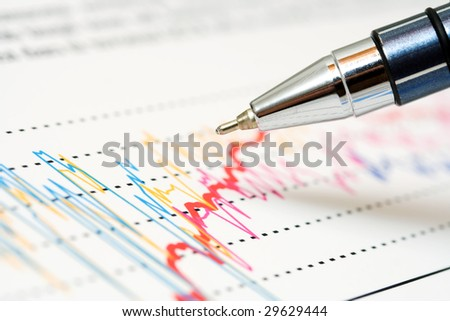 Ballpoint pen and stock market graphs. - stock photo