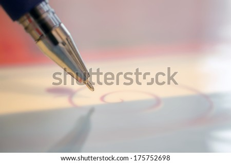 Ballpoint pen with gold tip, on a pink background. Closeup - stock photo