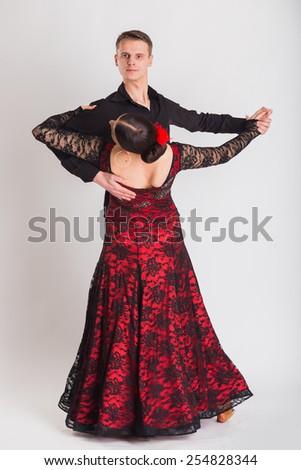 Ballroom dancing. Man and woman posing in dance pose on white. Man and woman dancing ballroom dances. Beautiful man and woman doing the dance steps. Dance poses. - stock photo