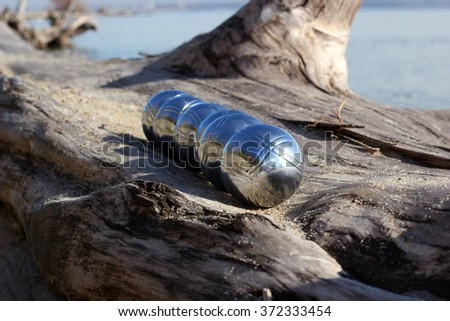Balls for petanque in a row on the log - stock photo