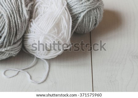 Balls of dark and light grey yarn on a white table.