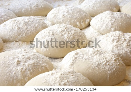 balls of dough covered with wheat flour ready for baking - stock photo