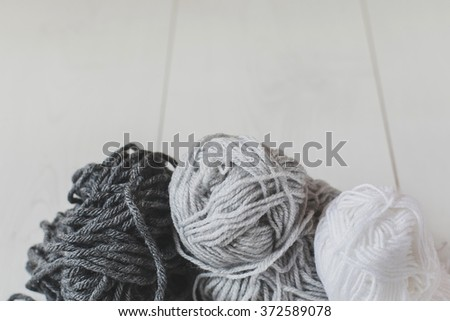 Balls of gray and white yarn on a white table.  - stock photo