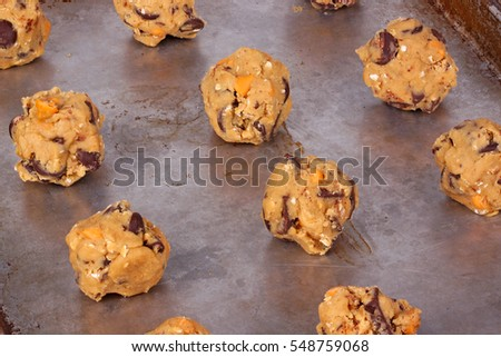 Balls of home-made chocolate and butterscotch chip and oatmeal cookie dough on a pan ready to be baked
