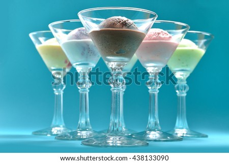 balls of ice cream in cocktail glasses on blue background