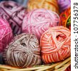 balls of knitted wool in basket, closeup - stock photo
