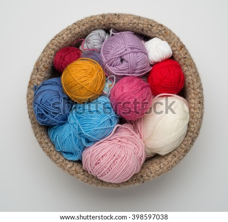 Balls of wool of different colours in a crocheted bowl on a white background. - stock photo