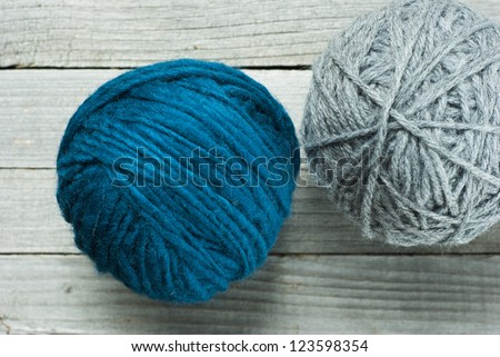 balls of wool on rustic wooden table background - stock photo