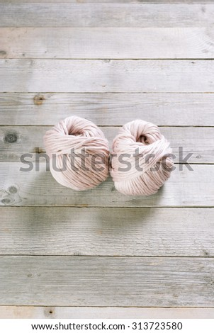 balls of wool on weathered wood table - stock photo