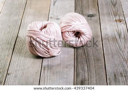 balls of wool on weathered wood table - stock photo