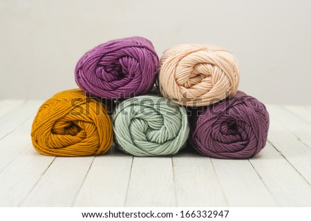 balls of wool on white wood surface