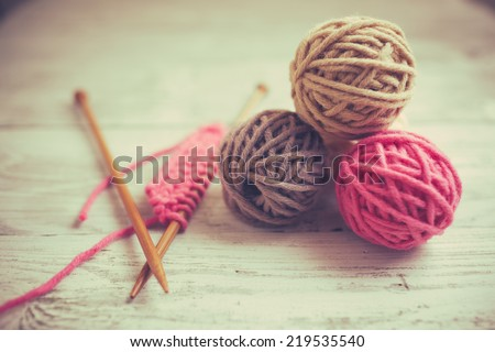 Balls of wool on wooden background, old retro vintage style - stock photo
