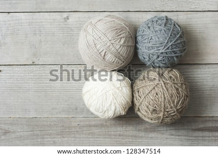 balls of wool on wooden table background, directly above - stock photo