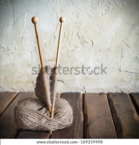 Balls of yarn and knitting on a wooden table. Retro style - stock photo