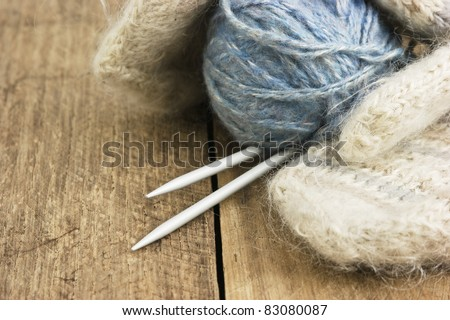 balls of yarn and mittens on a wooden background - stock photo