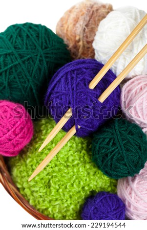 Balls of yarn in a basket with knitting needles isolated on white. Selective focus. - stock photo