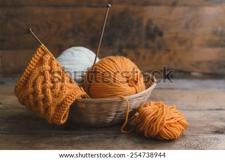 Balls of yarn in basket with knitting needles - stock photo