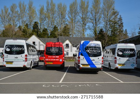 BALMAHA, LOCH LOMOND & TROSSACHS NATIONAL PARK, SCOTLAND, UK - 22 APRIL 2015: Tourism in Scotland - tour buses in the carpark of the National Park Visitor Centre, Balmaha on a hot day in spring