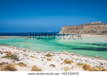 Balos lagoon on Crete island, Greece. Tourists relax and bath in crystal clear water of Balos beach. - stock photo