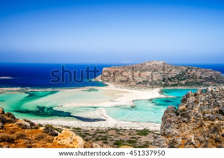 Balos lagoon on Crete island, Greece. Tourists relax and bath in crystal clear water of Balos beach. The sand is pink in the some parts of the beach. - stock photo