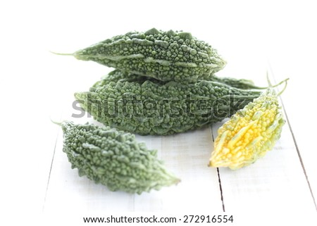 balsam apple (balsam pear, bitter cucumber, bitter gourd, bitter melon (Momordica charantia)) on wooden white background - stock photo