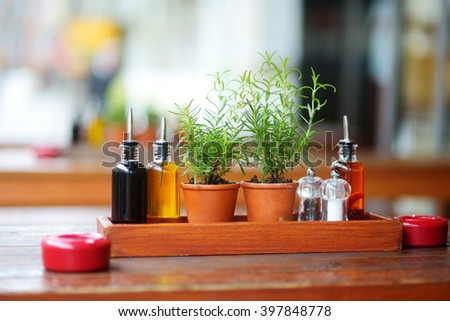 Balsamic vinegar and oil bottles and condiments on the table in an outdoor cafe - stock photo
