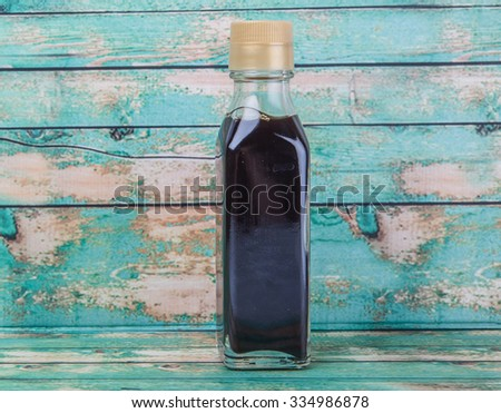 Balsamic vinegar in a glass bottle over wooden background - stock photo