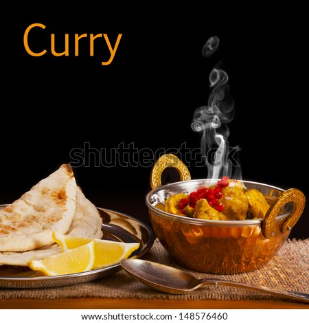 Balti dish with chicken curry with visible steam rising, served with naan bread and lemon, on a black background with space for text. Front to back focus.  - stock photo