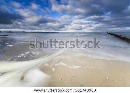 Baltic Sea at nightly light and long exposure, Undergoing sun irradiates the sea and stones in the sea water, Moving lake and foaming waves on the shore,