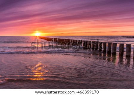 Baltic sea coast at colorful sunset with wooden groyne, Poland