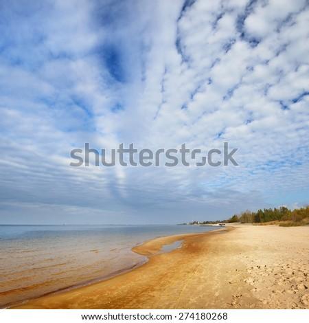 Baltic sea shore and ornamental clouds in Riga, Bolderaja - stock photo