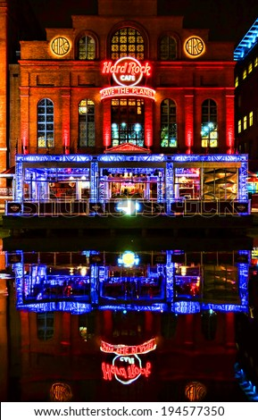 Baltimore, Maryland - Circa 2014: Hard Rock Cafe restaurant and music entertainment bar facade storefront with bright colorful neon signs and reflections in the water at night