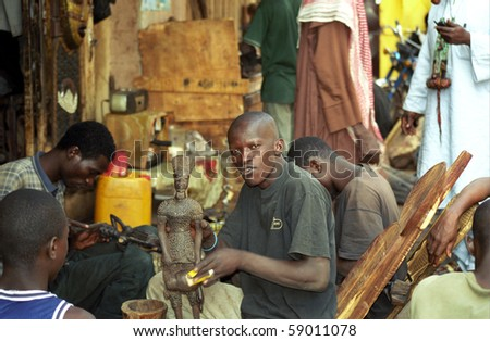 BAMAKO, MALI - JANUARY 17: Local artist sells his staff at the market at January 17, 2006, Bamako, Mali. Carving is popular in West Africa and tourists like them as well.