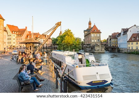 BAMBERG, GERMANY - MAY 7: Passenger ship at river Regnitz in Bamberg, Germany on May 7, 2016. Bamberg is a UNESCO world heritage site. Foto taken from Am Kranen with view to the town hall. - stock photo