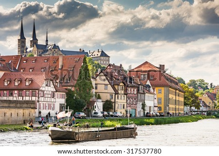 BAMBERG, GERMANY - SEPTEMBER 4: Tourists at the river Regnitz below Michelsberg Abbey in Bamberg, Germany on September 4, 2015.  The historic city center of Bamberg is a UNESCO world heritage site.  - stock photo