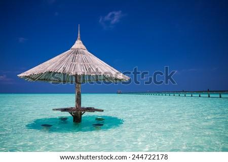 Bamboo beach umbrella with bar seats in the water at Maldives - stock photo
