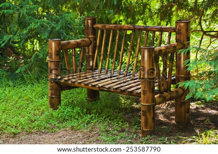 Bamboo bench in a green summer forest, sunny landscape background - stock photo